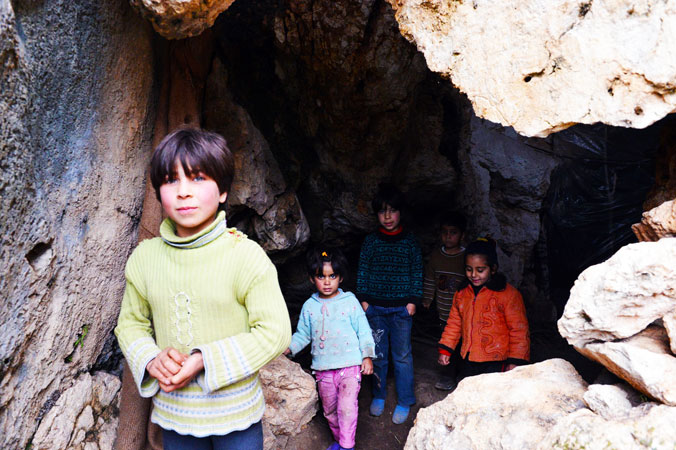 Syrian children stand at the entrance of a cave in which they refuged in Ain al-Zarka, northeast of Syria. The caves scattered along the sheer cliffs in this picturesque region became makeshift homes for refuges from the incessant regime shelling.