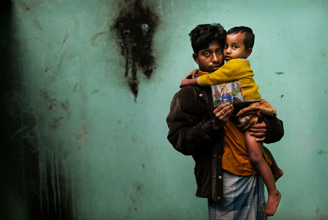 Bangladeshi Abdul Jabbar holds his son Masum, as he displays a photograph of his wife Mahfouza Kahtun, a sewing machine operator who died in the fire at Tazreen Fashions. The fire drew international attention to the conditions that garment workers toil under in Bangladesh, where the $20 billion-a-year textile industry is incredibly powerful and politically connected.