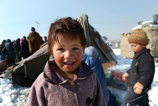 An Afghan child smiles as his mother receives winter supplies in Kabul on January 1, 2013. Over a third of Afghans are living in abject poverty, as those in power are more concerned about addressing their vested interests rather than the basic needs of the population, a UN report said. ? AFP Photo