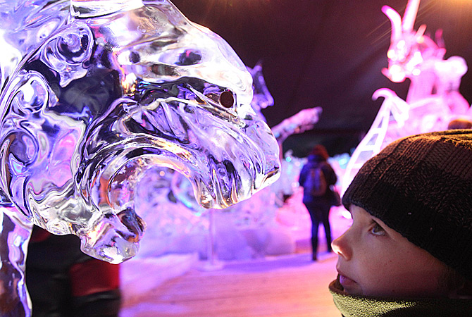 A boy looks at a tiger made of ice, at the Ice Sculpture festival in Bruges, Belgium, Friday, January 4, 2013. ? AP Photo