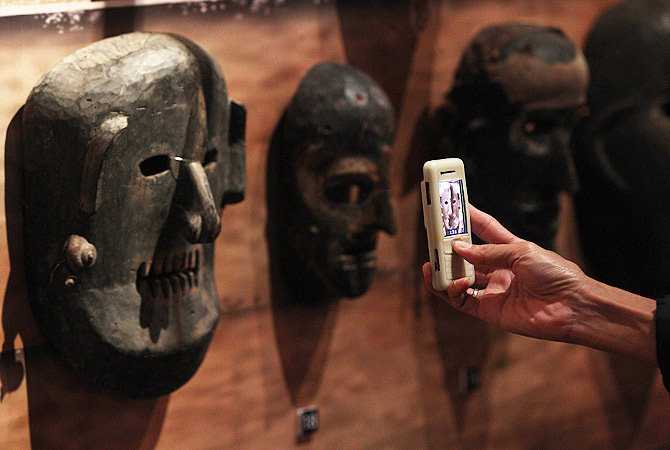 A visitor takes pictures of a wooden mask at the Masks of the World exhibition at the National Museum in Kuala Lumpur. ? AFP Photo