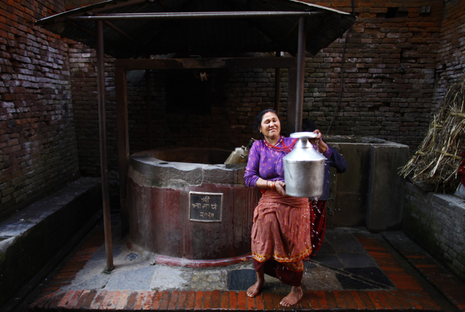 A Nepalese woman carries a container filled with water from a well at Bhaktapur, Nepal.