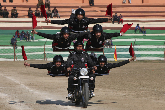 Indian policemen perform a stunt on a motorcycle during the Republic Day parade in Jammu January 26, 2013. India celebrated its 64th Republic Day.
