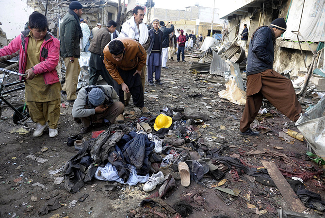 Local residents look at clothes left in a pile at the site of overnight twin suicide bombings in Quetta on January 11, 2013. – Photo by AFP