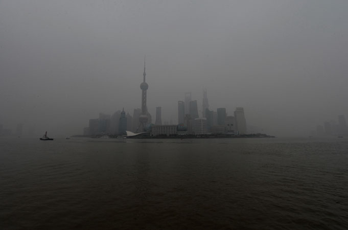 The Pudong business district is shrouded by heavy air pollution in Shanghai. Several days of hazardous air quality across large swathes of northern China triggered an emergency response which saw schoolchildren kept indoors, factories closed and government cars parked. ?Photo by AFP