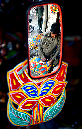 A Pakistani artisan reflected in a truck mirror works on making decorations for trucks and cars, in Rawalpindi. — AFP Photo