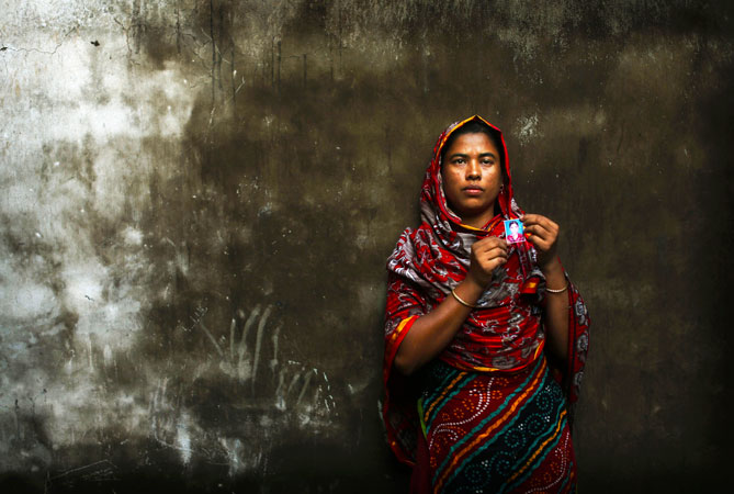 Bangladeshi Rumana Begum holds a photograph of her 18-year-old daughter Mukhtar Begum, a senior sewing machine operator who died in the fire.