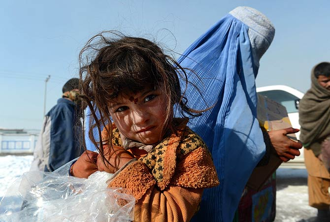 An Afghan girl walks as she receives winter supplies in Kabul on January 1, 2013. Over a third of Afghans are living in abject poverty, as those in power are more concerned about addressing their vested interests rather than the basic needs of the population, a UN report said. ? AFP Photo