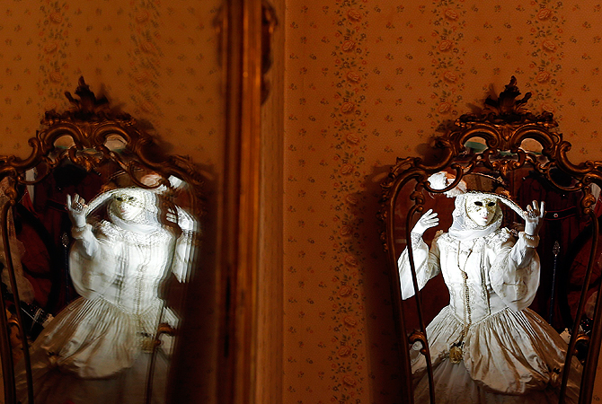 Nadia, wife of Marco Dilauro, is reflected in mirrors as she wears one of his creations, an elaborate costume for the Venice. ? Reuters Photo