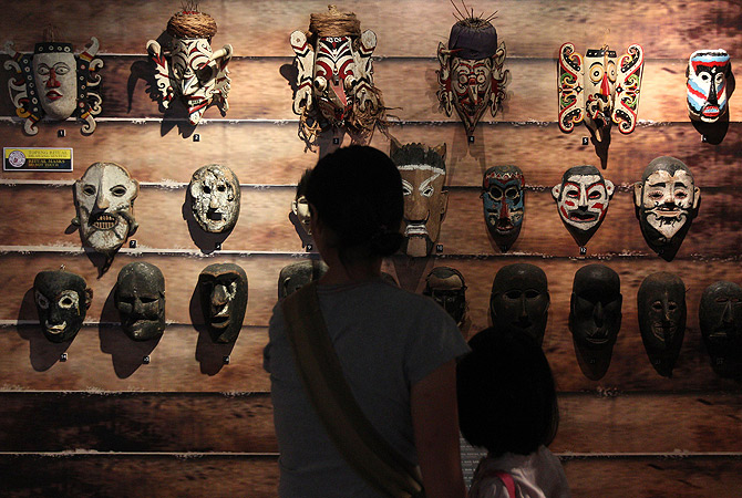 Visitors look at various wooden masks on display for the Masks of the World exhibition at the National Museum in Kuala Lumpur on January 5, 2013. ? AFP Photo
