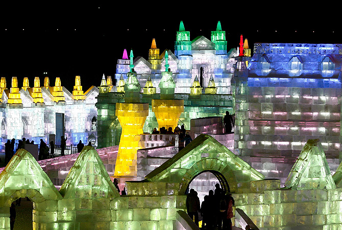 Visitors walk through ice sculptures during the official opening of the 29th Harbin International Ice and Snow Festival in Harbin in northeast China's Heilongjiang province. ? AP Photo