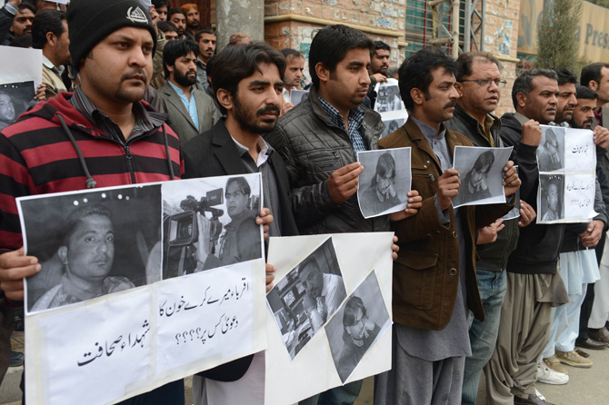 Pakistani media representatives hold pictures of killed journalists during a protest in Quetta on January 11, 2013, against the bomb attacks. – Photo by AFP