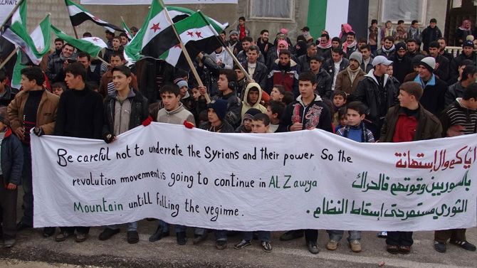 Youths hold a banner during a protest against Syria's President Bashar al-Assad, in Jabal Al-Zawiya near Idlib, in this picture provided by Shaam News Network and taken January 11, 2013. Picture taken January 11, 2013. – Photo by Reuters