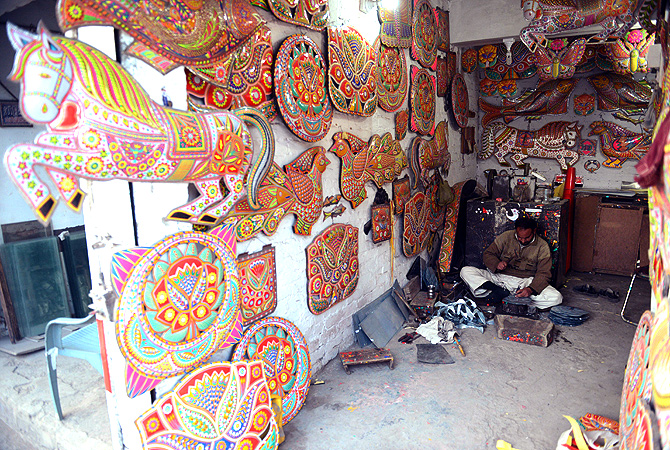 A Pakistani artisan works on making decorations for trucks and cars, in Rawalpindi. — AFP Photo