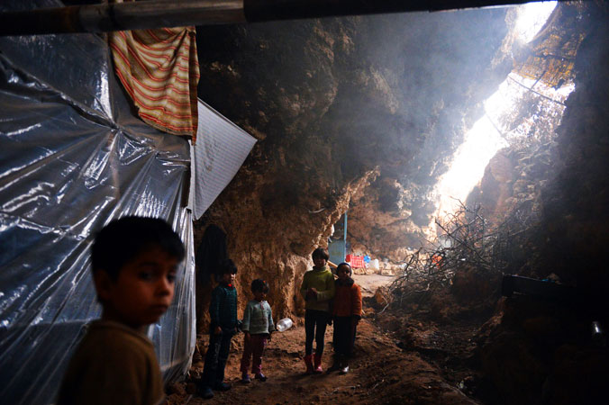 Syrian children stand inside a cave, now their living area.