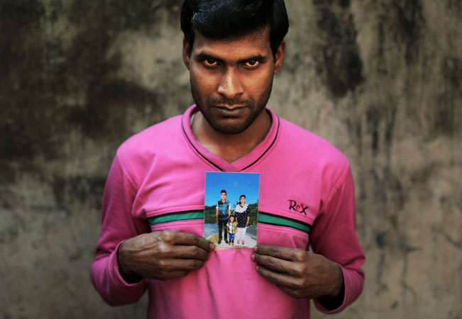 Bangladeshi Mohammed Habibur displays a photograph of his wife Rashida Akhtar, a sewing machine operator who died in the fire.