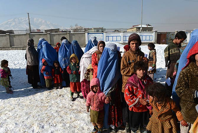 Afghan women with their children line-up to get winter supplies in Kabul. ? AFP Photo