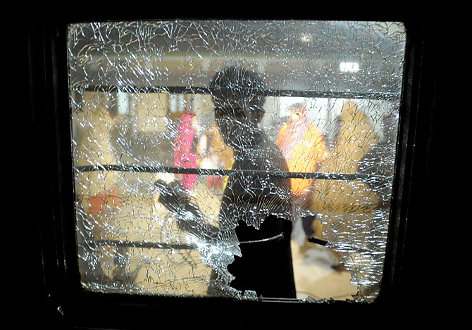 A Pakistani man walks past a broken mirror on the Jaffar Express train after an attack at a railway station in Quetta