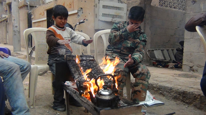 Boys warm themselves around a fire in Deir Al-Zor, in this picture provided by Shaam News Network and taken January 8, 2013. Picture taken January 8, 2013. – Photo by Reuters