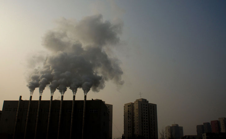 Heavy smoke coming out from chimneys in the Wangjing community, Beijing. Shares of a Chinese face mask manufacturer soared as investors looked for opportunities to cash in on the severe air pollution. ?Photo by AFP