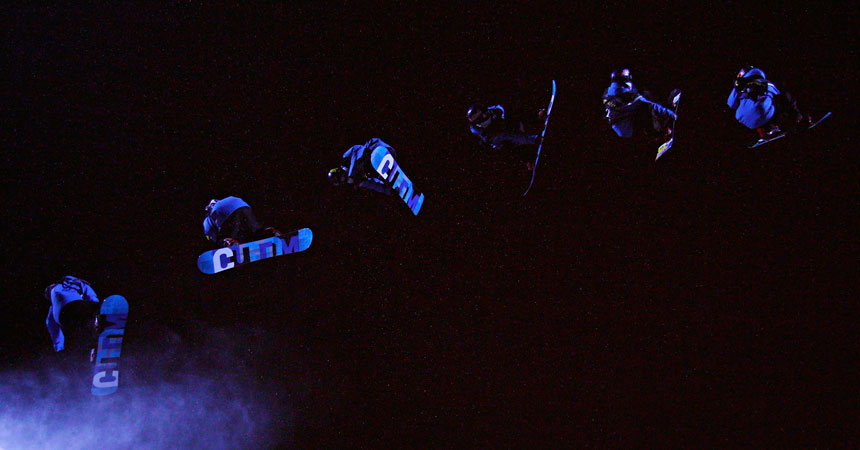 Snowboarders fly in the air during the men