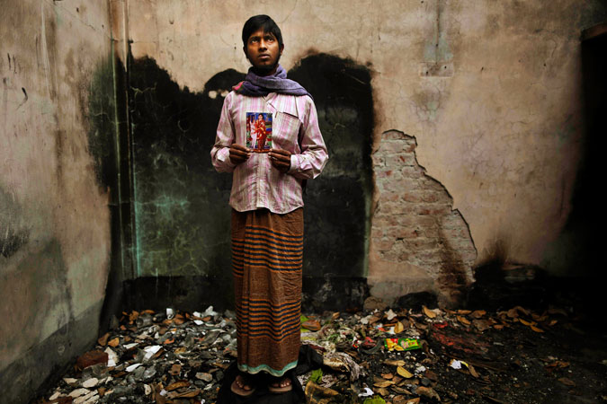Bangladeshi Saddam Hussein, holds a photograph of his wife 20-year-old Mitu Begum, a sewing machine operator who died in the fire.