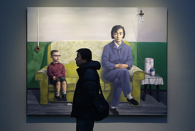"A man walks past an oil painting titled 'My Mother' by Chinese artist Zhang Xiaogang from his ""Amnesia and Memory Series"", during the Beijing Voice exhibition at Pace Beijing Gallery in Beijing's 798 art zone.  Zhang is a 54-year-old painter who has been crowned with many titles, such as ""Chinese contemporary art icon"" and ""China's most expensive living painter"". Since the start of his very successful Bloodline - Big Family series in the mid-1990s, Zhang has witnessed and experienced a particular history of China,"