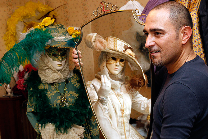 Marco Dilauro looks on as his wife Nadia is reflected in a mirror as she wears one of his creations. ? Reuters Photo