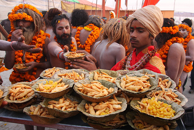 "Indian members of Akhara distribute food to Indian Hindu Saddhus (holy men) after a religious procession of the first ""royal entry"" of the Kumbh Mela at the Sangam in Allahabad on January 3, 2013. The Kumbh Mela, which is scheduled to take place in the northern Indian city in January and February 2013, is the world's largest gathering of people for a religious purpose and millions of people gather for this auspicious occasion. ? AFP Photo"