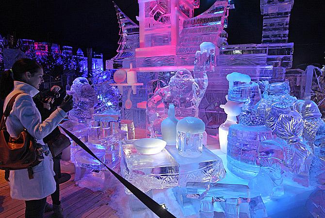 A visitor takes a photo of a scene titled: 'the Valley of the Dwarfs', at the Ice Sculpture festival in Bruges, Belgium, Friday, January 4, 2013. ? AP Photo