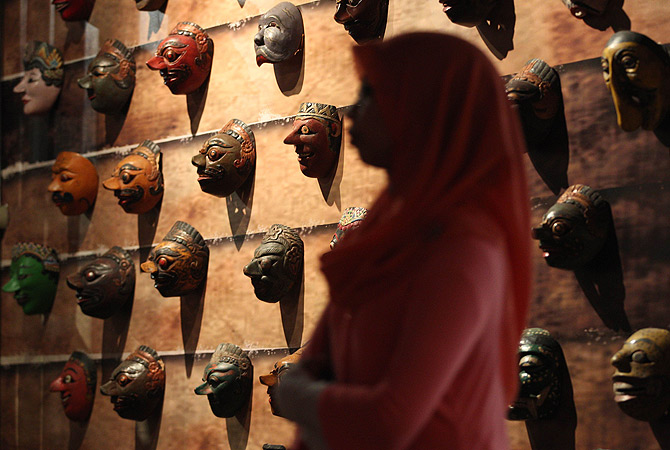 A visitor walks past various wooden masks Javanese and Balinese culture in Indonesia displayed during the Masks of the World exhibition at the National Museum in Kuala Lumpur on January 5, 2013. ? AFP Photo