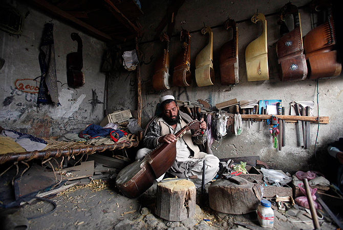 A man repairs a rabab, a traditional musical instrument, at his workshop in Peshawar January 8. 2013. ? Reuters Photo