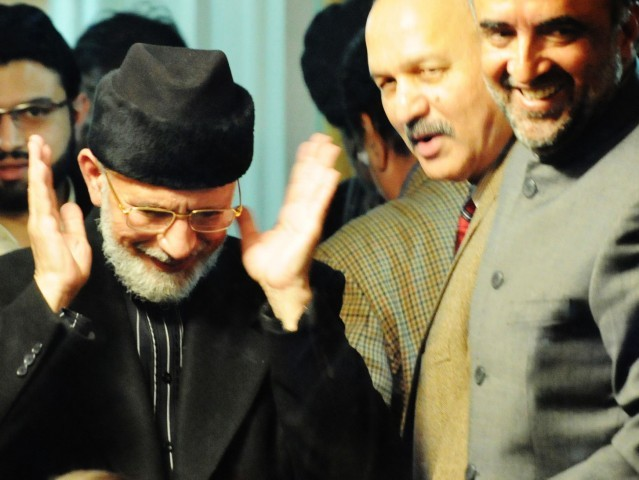 Qadri shares a joke with the government's negotiation team that met him on the fourth day of his 'long march.'