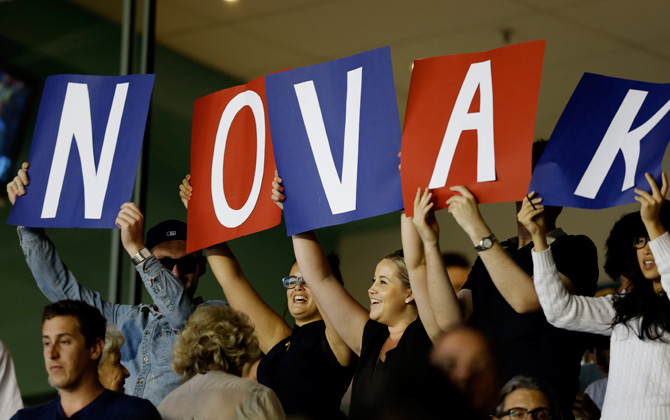 Supporters of Serbia's Novak Djokovic holds up banners during his quarterfinal match against Tomas Berdych of the Czech Republic at the Australian Open tennis championship in Melbourne, Australia, – Photo by AP