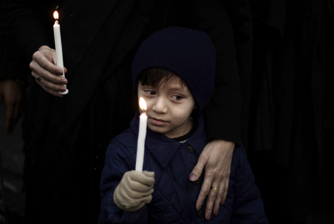 ) A boy holds a candle while he and his mother take part in a protest to condemn Thursday's deadly bombings in Quetta, in Islamabad, Pakistan, Friday, January 11, 2013. – Photo by AP