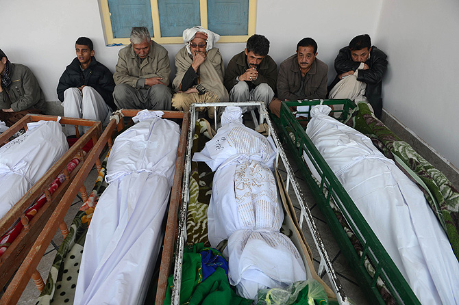 Pakistani Shiite Muslim mourners sit beside the coffins of blast victims at a mosque following overnight twin suicide bombings in Quetta on January 11, 2013. – Photo by AFP