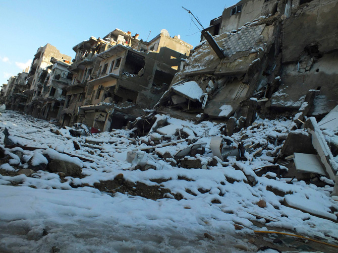 Damaged buildings covered with snow are seen at Jouret al Shayah area in Homs January 10, 2013. Picture taken January 10, 2013. – Photo by Reuters)
