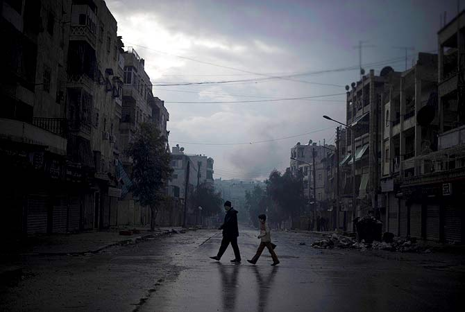 "A father and son return home with vegetables, as smoke from a pro-government forces artillery strike ascends in the background, in the al-Amaria neighbourhoodin the city of Aleppo, on January 6, 2013.  Syria's embattled President Bashar al-Assad in a rare televised speech denounced the opposition as ""slaves"" of the West and called for a national dialogue conference to be followed by a referendum on a national charter and parliamentary elections. ? AFP Photo"
