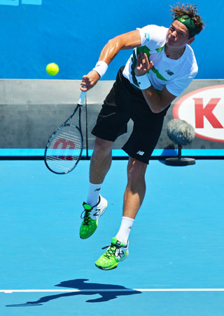 Canada's Milos Raonic serves against the Czech Republic's Jan Hajek during their men's singles first round match.