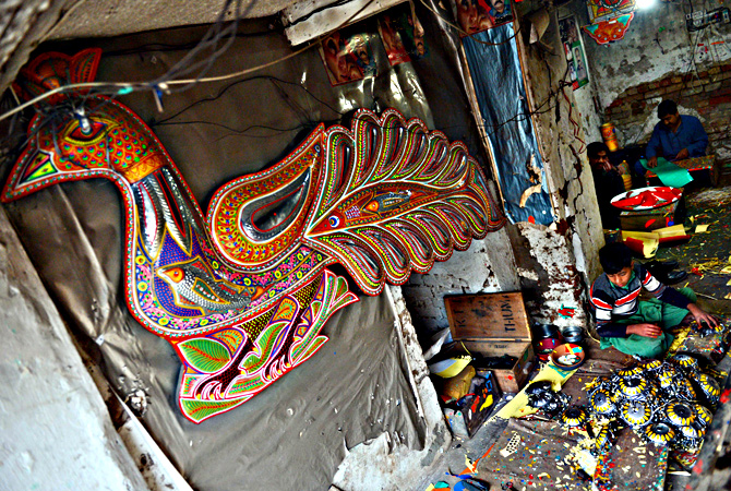 Pakistani artisans work on making decorations for truck and cars, in Rawalpindi. — AFP Photo