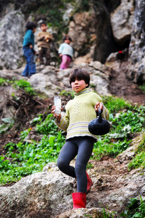 A Syrian girl climbs down the dangerous rocks, holding a kettle and cups.