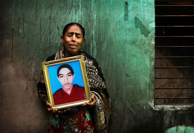Bangladeshi Rokeya Begum displays a photograph of her 18-year-old daughter Henna Akhtar, a sewing machine helper who died in the fire.