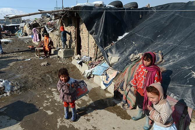 An Afghan child stands outside her tent after she receives winter supplies in Kabul on January 1, 2013. ? AFP Photo