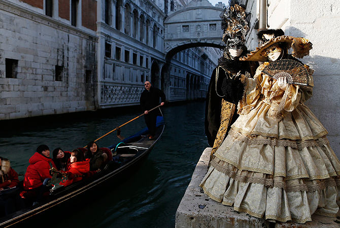 Marco Dilauro and his wife Nadia, wearing costumes, pose at a canal with the Bridge of Sighs in the background during the Venice Carnival. ? Reuters Photo