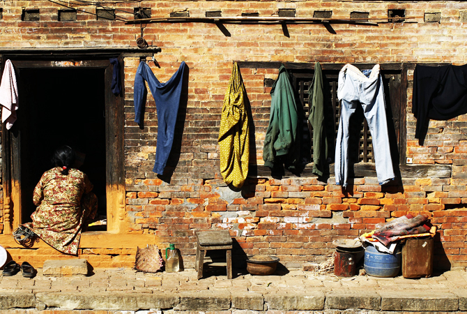 A Nepalese woman sits in the doorway of her house at Bhaktapur, Nepal.