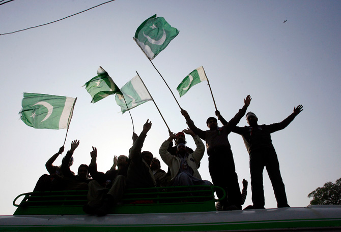 Supporters wave flags on top of a bus during a protest march from Lahore to Islamabad January 13, 2013. ? Photo by Reuters