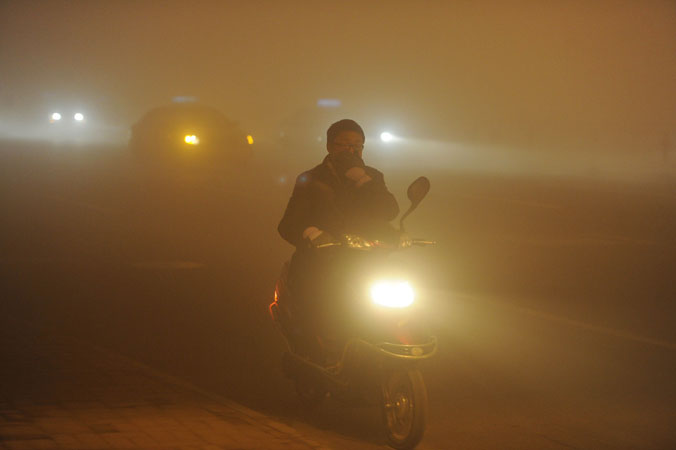 A man covering his mouth with his hand as he rides amidst the heavy fog in Hefei, central China's Anhui province. ?Photo by AFP