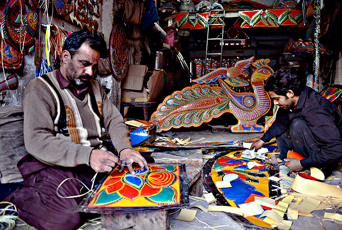 A Pakistani artisan works on making a decoration for a truck or car, in Rawalpindi. — AFP Photo