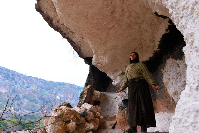 A Syrian woman Najah Gafari (L), 55, builds a wall with rocks to protect the entrance of a cave she is living with her family.