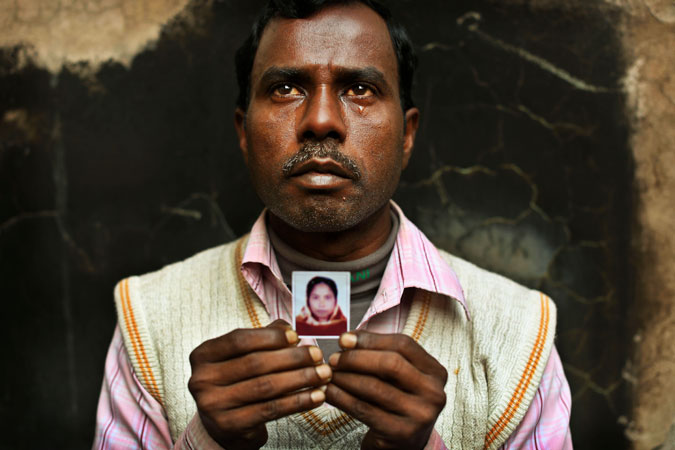 Bangladeshi Mohammed Hannan weeps as he holds a picture of his wife Ahenur, an assistant sewing machine operator who died in the fire.